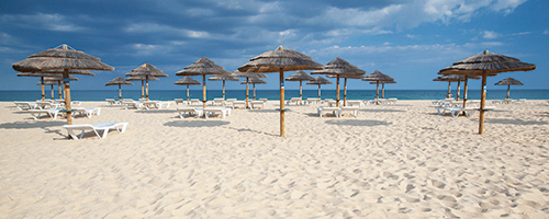 Different parasols and sun loungers on the empty beach on Tavira